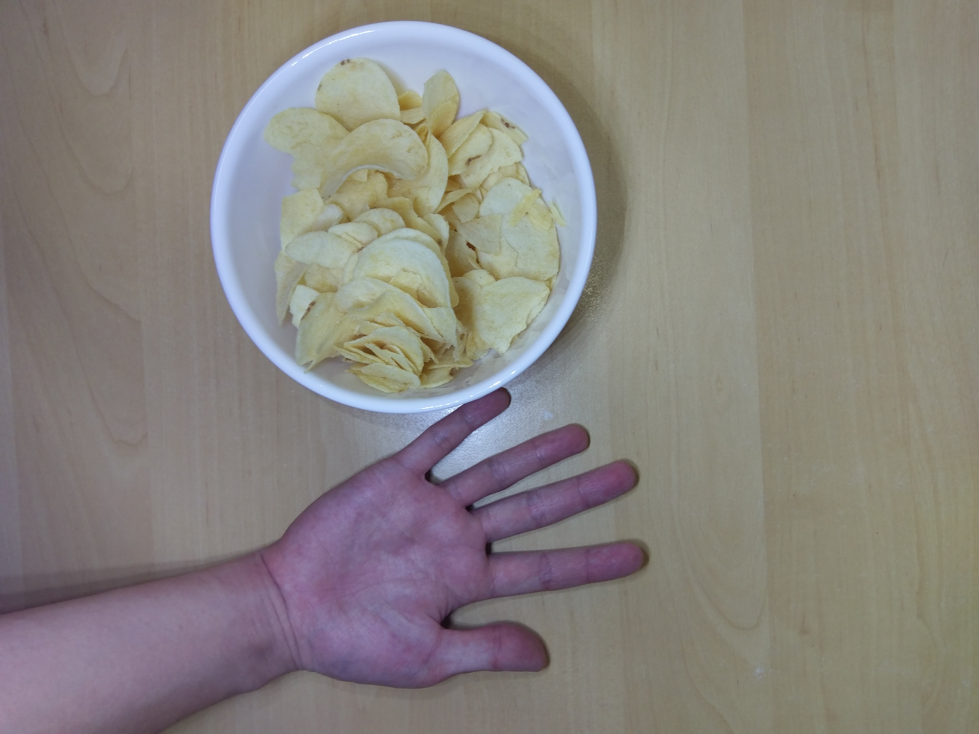 Cosmos Yogurt potato chips emptied into a bowl. My hand for size comparison.